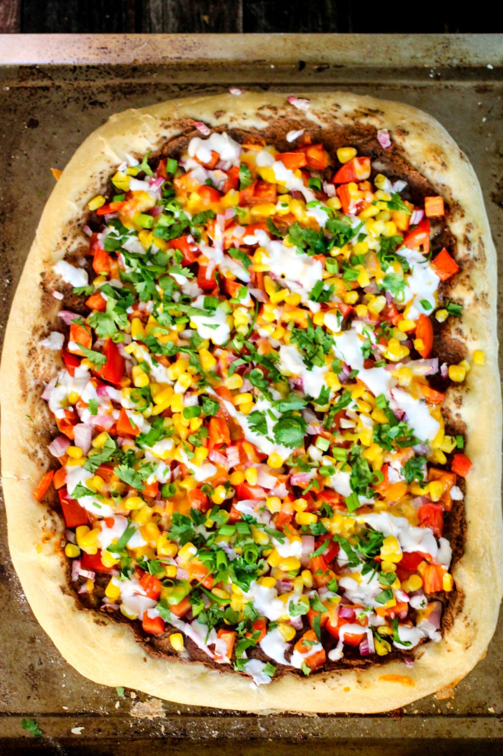 Making homemade pizza is a cinch with pre-made dough and healthy fresh ingredients! This Southwest Pizza is loaded with beans, corn, tomatoes, red onion, and a lime cream!