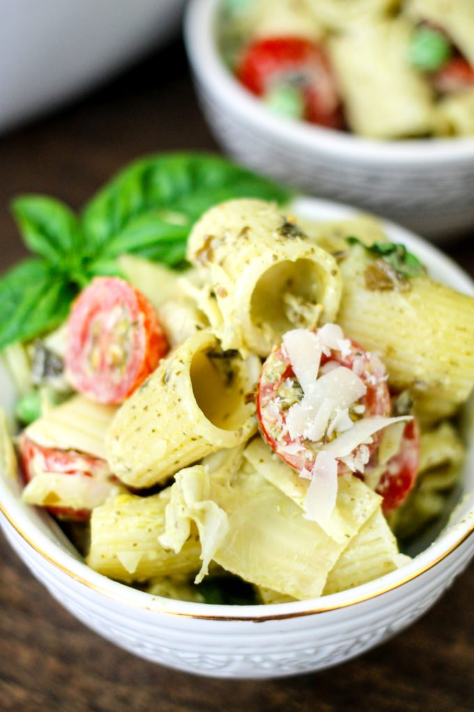This Creamy Pesto Pasta Salad is full of tomatoes, artichokes, peas, and topped with a creamy pesto sauce! It's sure to be a BBQ favorite!