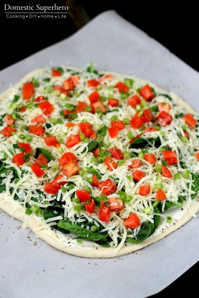 Easy Homemade Pizza is the perfect weeknight meal or game day appetizer! Load it up with Spinach, Tomatoes, and Ranch for a delicious pizza!