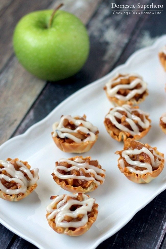 One Bite Apple Pie Tartlets topped with a delicious cream cheese glaze! Perfect for fall!