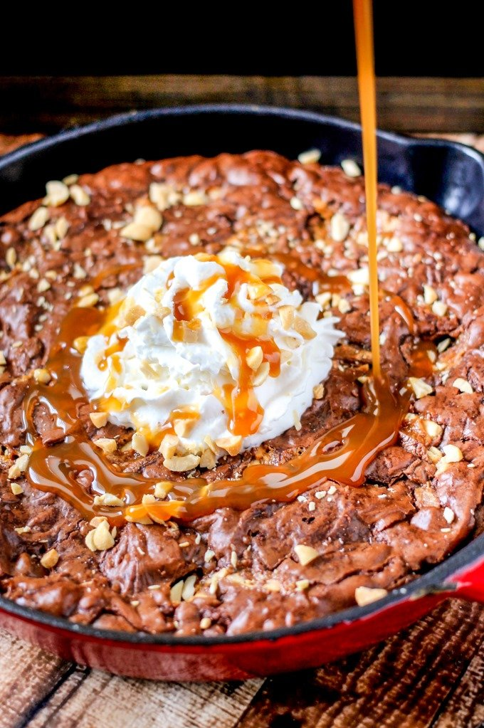 SNICKERS Skillet Brownies are ooey-gooey and full of chocolate, peanuts, and caramel. So easy to make and seriously delicious!