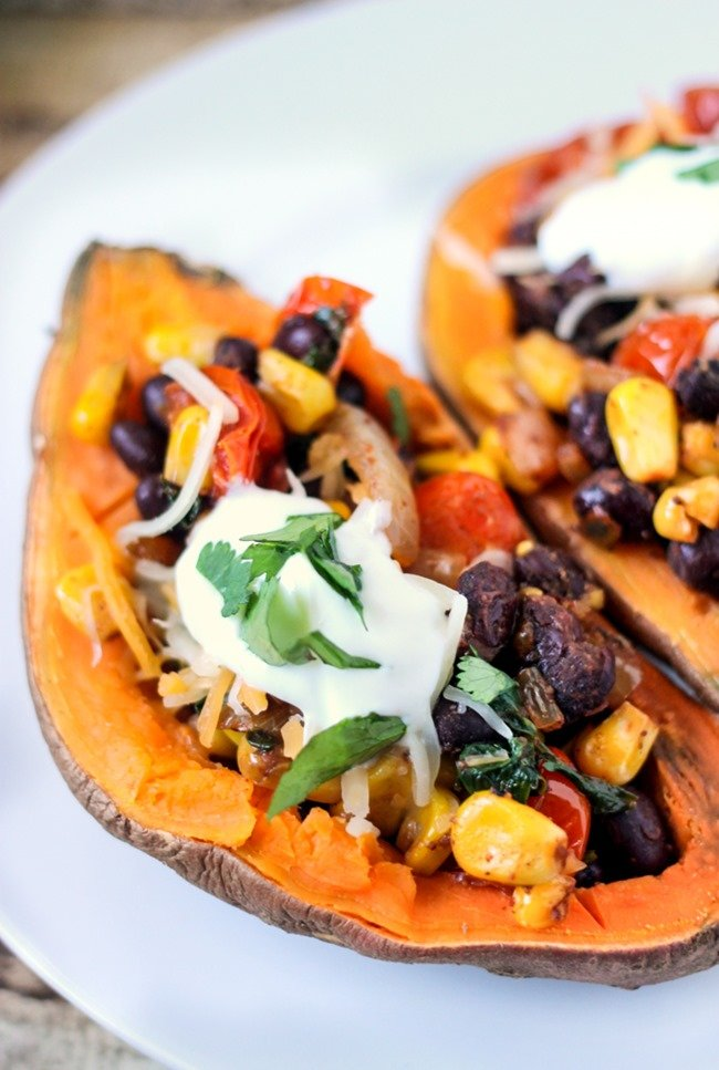 Vegetarian Southwestern Stuffed sweet potatoes are full of beans, corn, and spices! A dash of lime and cilantro and you have one kicked up healthy meal! These bad boys only have 230 calories for a WHOLE (2 halves) potato!!! Total win!