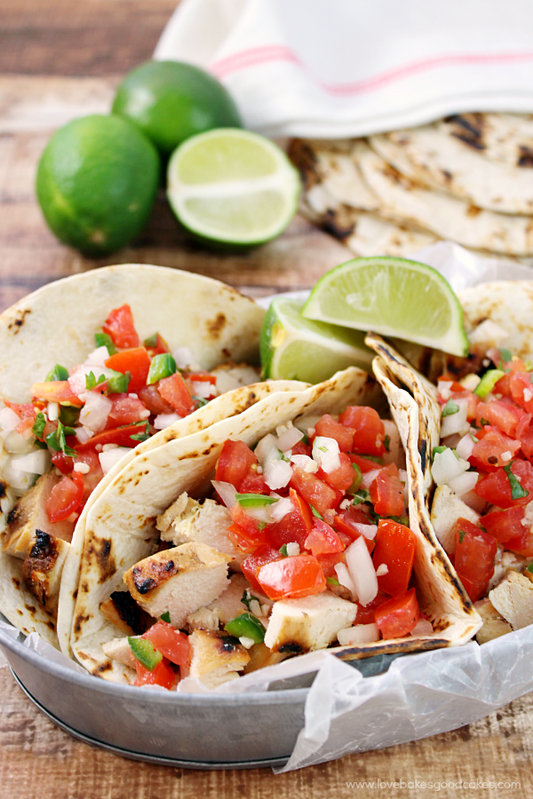 Grilled Chicken Fresco Tacos in a metal pan with fresh limes.