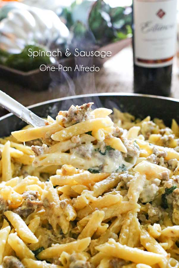 A close up of spinach sausage one pan alfredo in a skillet