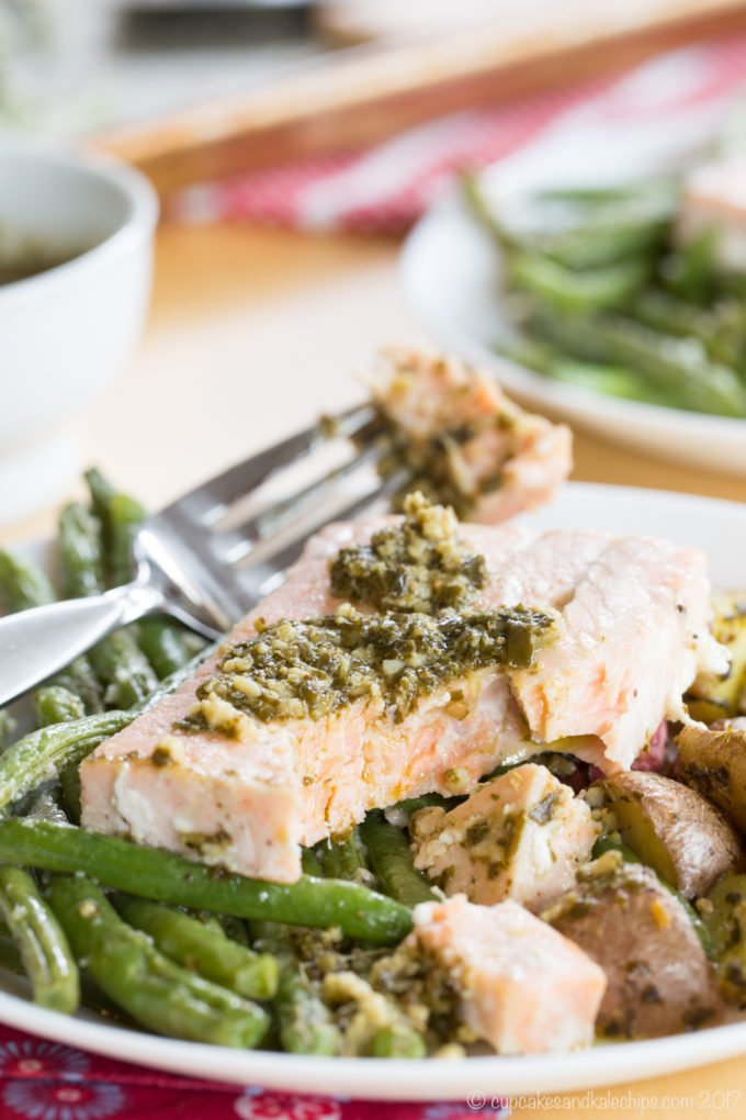 A close up of a plate of pesto salmon on a sheet pan