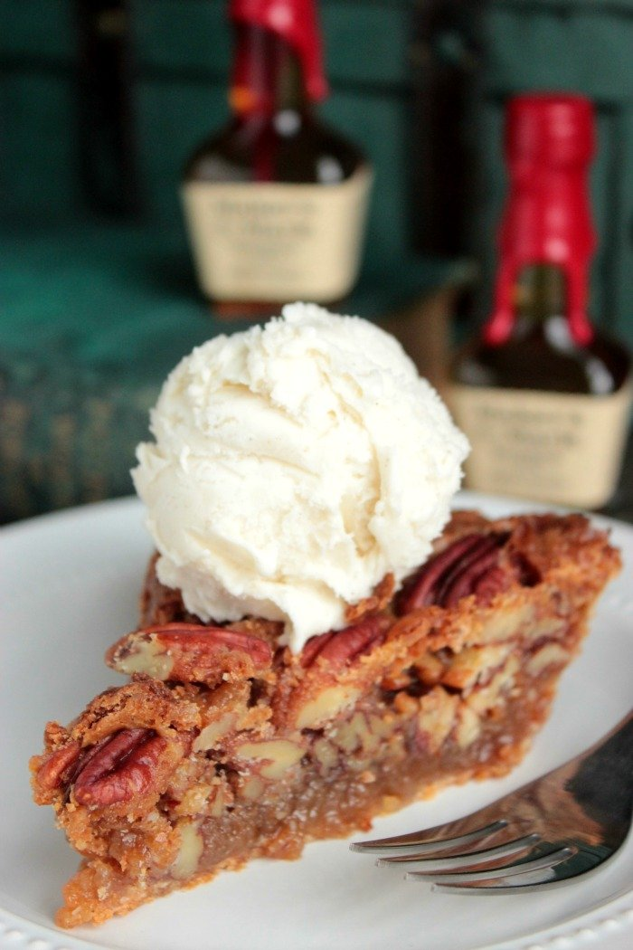 Slice of Bourbon Pecan Pie on a white dessert plate topped with ice cream