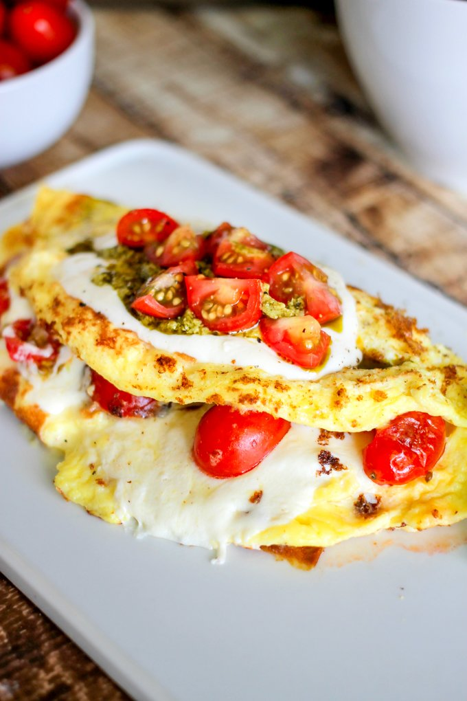 This Caprese Omelette is filled with balsamic drenched fresh tomatoes, basil pesto, and mozzarella cheese. Whip this up for the perfect breakfast or brunch.